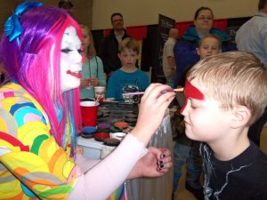 "Hunter Williams, 7, of Sartell, gets his face painted at the ""Just 4 Laffs"" booth at Sartell Community Expo."