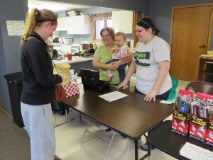 photo by Cori Hilsgen Albany resident Rachel Ramacher, 15, visits with Susan Curtis, one-year-old Amelia Curtis and Alana Curtis (left to right) at the Resurrection Lutheran Church garage sale.
