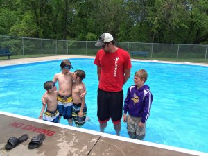 photo by Dennis Dalman YMCA lifeguard Tim Immelman of Sartell stands with pool visitors June 9 at the wading pool in Watab Park. Left to right are brothers Jacob, Anthony and Caleb Larson of Sauk Rapids and Oliver Eikmeier of Sartell. The grandmother of the Larson boys, Barbara Mills of St. Cloud, said she was babysitting her grandsons and decided they would enjoy some cool fun at the Watab pool.