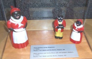 "photo by Dennis Dalman These figurines, based on the iconic ""Aunt Jemima"" pancake products, include a syrup dispenser (left) and salt-and-pepper shakers (right). The ""male"" shaker is supposed to be Aunt Jemima's husband and resembles the demeaning ""Stepin Fetchit"" character so often depicted in movies before the Civil Rights Era. This is one of the many exhibits in ""For All the World to See,"" now showing at the Stearns History Museum."