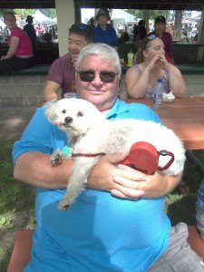 photo by Dennis Dalman Jeff Tinklenberg of St. Cloud holds his buddy, Pattie, at River Days Food Fest June 27 in Sauk Rapids.